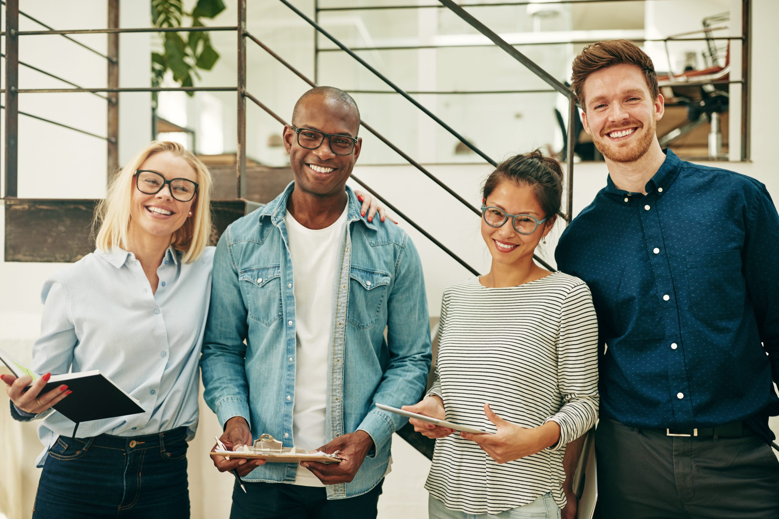 Group of diverse young businesspeople laughing together while standing side by side in a bright modern office